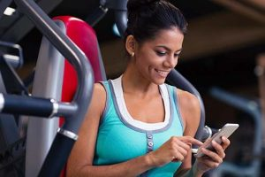Woman in gym using smartphone