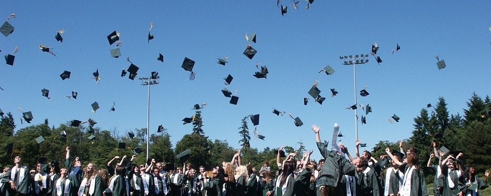 students at graduation throwing caps in the air