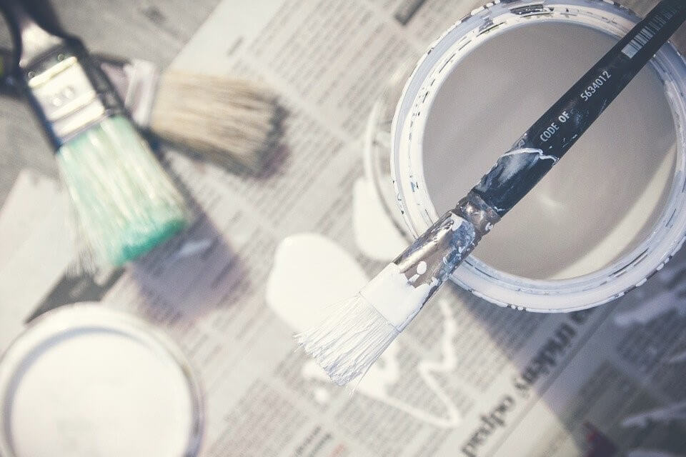 can of paint with several brushes