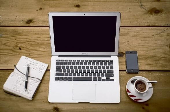 wooden table with a laptop and coffee cup-saucer